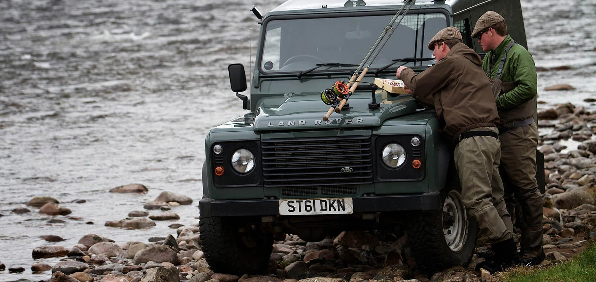 Fisherman next to Landrover by the riverside